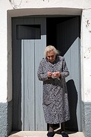 Old lady at her house´s door, town of Castaño del Robledo, province of Huelva, Andalusia, Spain