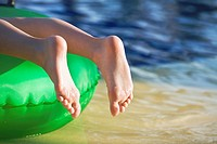 Young girl lying on green float with toes pointed at waters edge