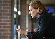 Businesswoman texting while waiting for train
