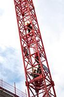 firemen climbing a tower crane
