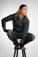 Asian man with dreadlocks crouching on a stool
