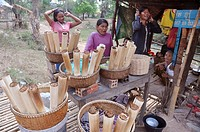 Siem Reap (Cambodia): women selling traditional Cambodian sweets, made with sticky rice, beans paste and coconut pulp, cooked in bamboo sticks