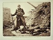 Belgian soldier looking at dead German soldier killed in action in trench at Diksmuide in Flanders during the First World War, Belgium