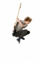 Teenage boy jumping in the air while playing bass guitar