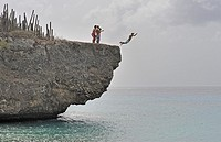 Kids jumping off cliff into ocean, Bonaire Island, Netherlands Antilles, Caribbean