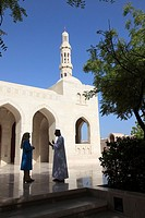 Omani man and woman talking outside in front of Grand Mosque Sultan Qaboos, Muscat, Sultanat of Oman, Asia.