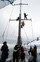 Tourists climbing the rigging on yacht Pelagic in the Lemaire channel,Antarctic peninsula