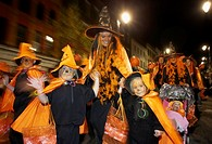 schoolchildren and teachers dressed as orange pumpkins parade down shipquay street Halloween Derry Ireland