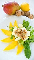 Salad with cheese, mango, lettuce, lemon and mint leaves