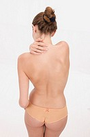 young woman in apricot transparent panties with pain in her neck