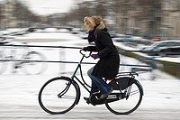 Woman cycling in winter, Amsterdam, the Netherlands