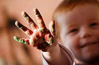 The hand of a toddler with red hair, shwoing hand after finger painting