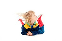 boy with long blond hair lying on the floor - isolated on white