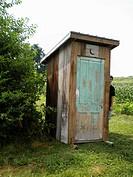 Boy Peeking Around Outhouse