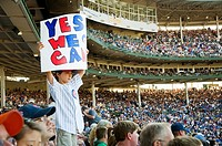 Young Chicago Cubs fan holding up positive message sign saying ´Yes We Can ´ at Wrigley Field