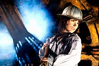 Representation of work in a mine made with a beautiful young woman with an aluminum hull pulling a steel cable with stained face and a dramatic lighti...