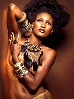 High fashion photo of a young beautiful woman wearing jewelry posing on brown background