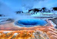 Crested Pool´s colors shine during the winter at Yellowstone National Park as Grand Geyser erupts in the background.