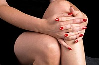 close view of woman´s hands folded across knees