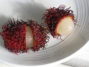 Rambutan fruit cut open on plate, Big Island, Hawaii, USA