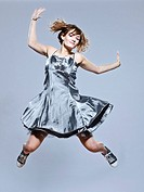 beautiful young caucasian woman girl evening dress jumping happy on studio isolated plain background