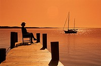 Silhouette of woman waiting on island pier with sailboat