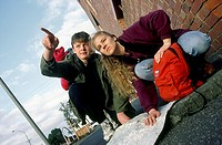 low angle view of couple of backpackers in street reading their map