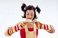 Beautiful Latina girl licking a cupcake, isolated
