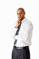 Handsome African Hispanic business man in white shirt, gray pants and tie, standing with hands on chin thinking, isolated