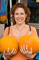 Woman holding two pumpkins at farmers´ market, Nevada City, California