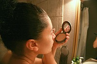Woman putting on makeup in a bathroom mirror
