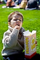 Little boy sitting in a grassy park eating popcorn