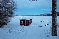 Small red cabin at the shore of a bay of the Baltic Sea in Sweden