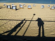 Shadows of people on the beach of Westerland, beach chairs and the North Sea in the background, Sylt, Germany