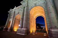 Night time view of the historic Puerta de Alcalá monument in the Plaza de la Independencia Madrid Spain