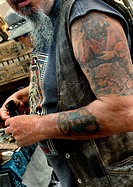 An old motorcyclist rider´s tattoos have not aged well.