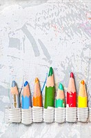 seven pencils arranged side by side against gray background