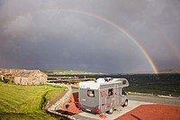 Uyeasound, Unst, Shetland Islands, Scotland, UK, Europe  Motorhome in Gardiesfauld youth hostel campsite with rainbow and grey clouds over the sea  Mo...