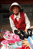 An old lady selling traditional style hand made embroidered shoes on old town street, Town of Guandu, Kunming, China