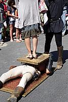 A performer at the wine festival in Fontes, France, entertains the crown by laying on a bed of nails as a woman stands on him during a street show