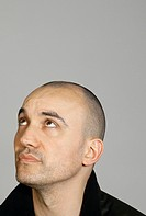 Studio shot of man with shaved head, looking upwards