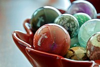 This stock image shows two white crosses reflected in a bowl of large, glass marbles  Background intentionally blurred for artistic effect