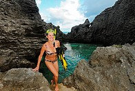 Woman coming out of ocean cove after snorkling, Bermuda Island, Atlantic