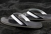 Black sandals on sand