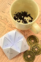 Where not to go for investment advice: Tea cup with tea leaves, Origami fortune teller - cootie catcher, Coins used with I-Ching laying on European fi...