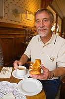 Man in his early 70s having coffee and cake Finland Europe