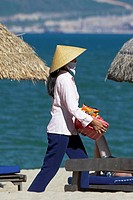 Woman beach vendor in conical hat walks between woven beach umbrellas Nha Trang south east Vietnam