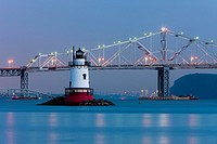 Twilight view of the Tarrytown Lighthouse and Tappan Zee Bridge on the Hudson River near the village of Sleepy Hollow, New York, with the skyline of M...