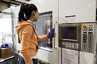 A woman creates Otterbox iPhone 5 exerior case covers at a plastic molding injection plant in Hudson, Colorado, USA