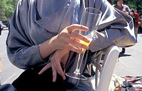 close up of a woman in high fashion at the races holding her glass of champagne and orange juice